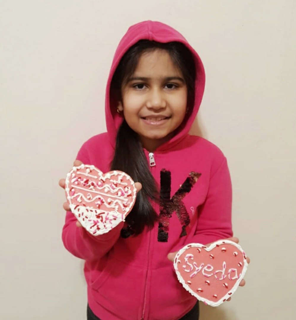 girl in pink sweatshirt holding her heart cookies