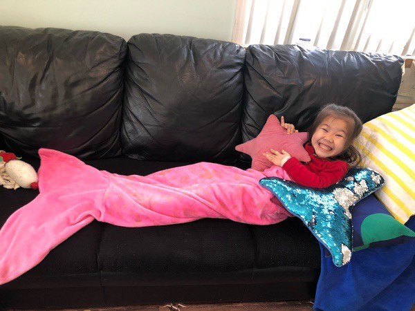 girl on couch with mermaid tail blanket