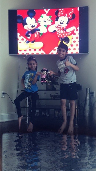 brother and sister pose in front of tv