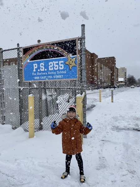 a student outside of the school playing in the snow