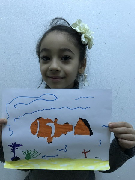 girl holding clown fish