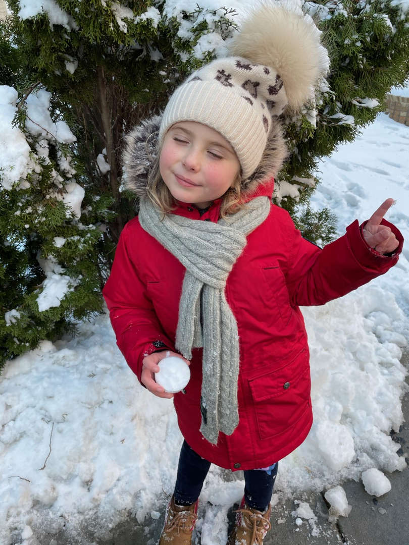 girl with red coat carrying a snowball