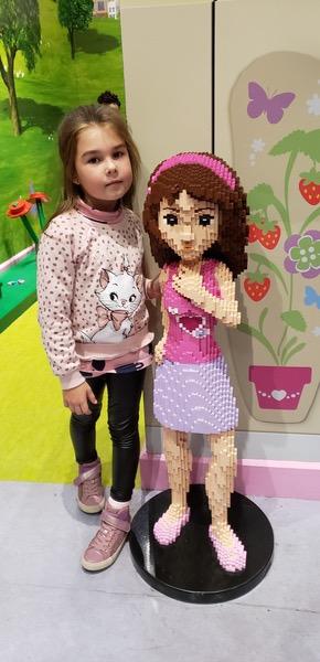 girl poses near large lego girl