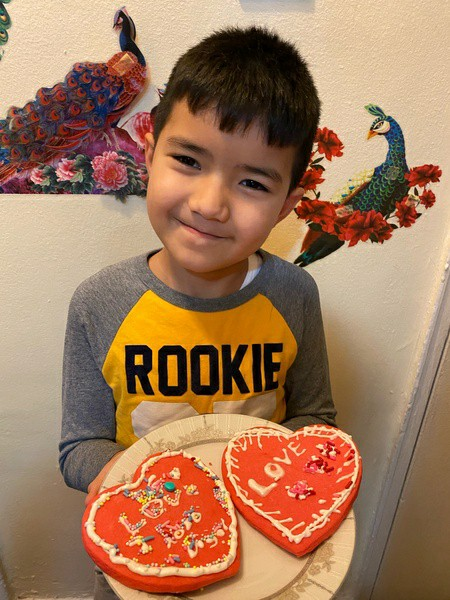 boy in yellow and gray shirt shows his decorated cookies