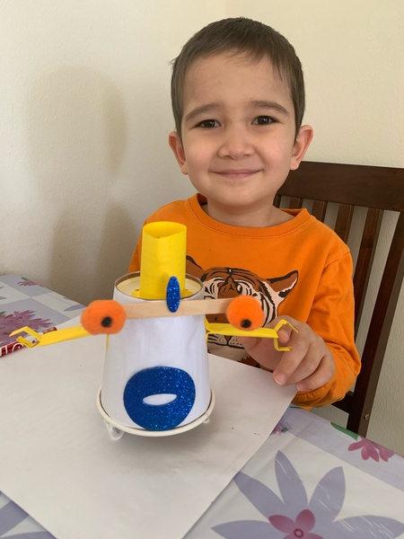 child in an orange shirt shows the monster he created