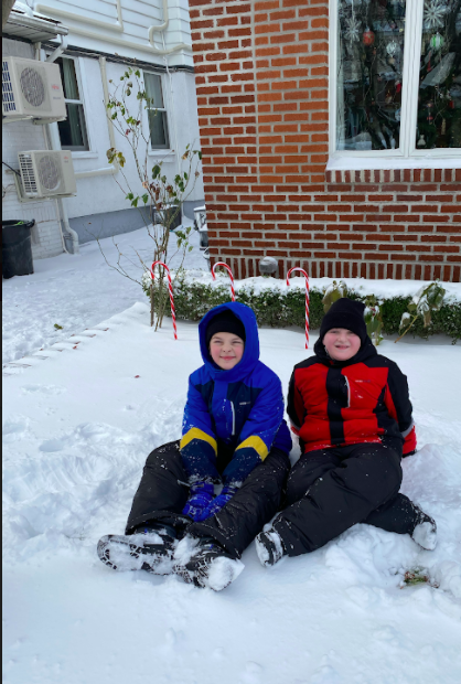 two friends sitting in the snow dressed warmly