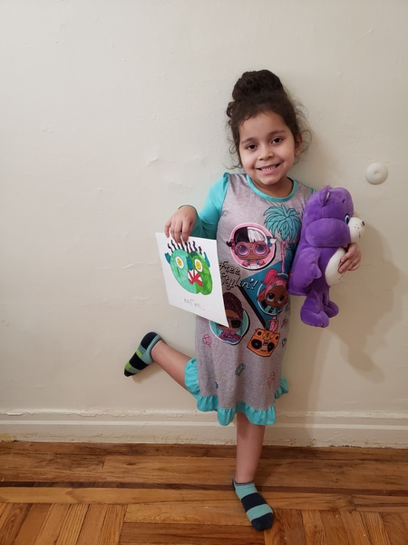 child standing holding drawing and purple care bear