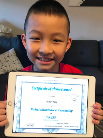 close up of a little boy holding his certificate on an iPad