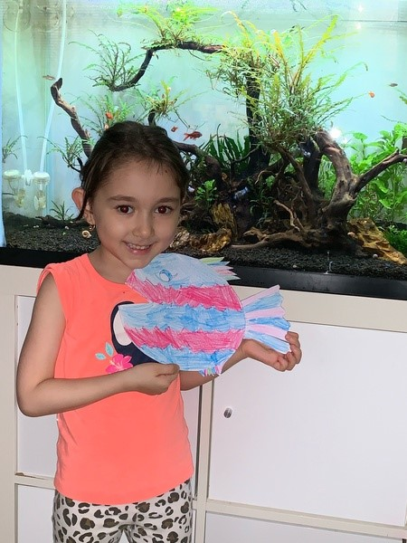 girl holding striped fish