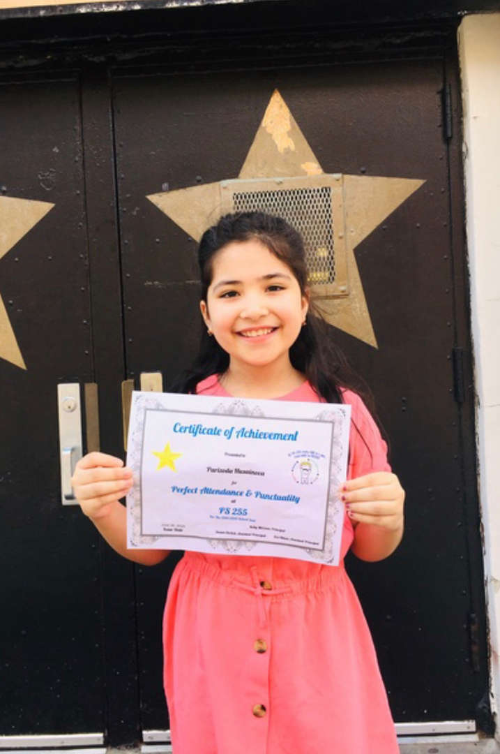 child holds color certificate in front of swinging doors that are closed
