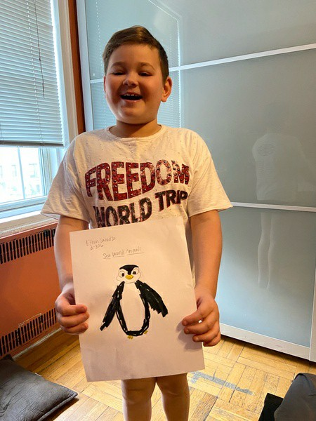 boy holds drawing of a penguin