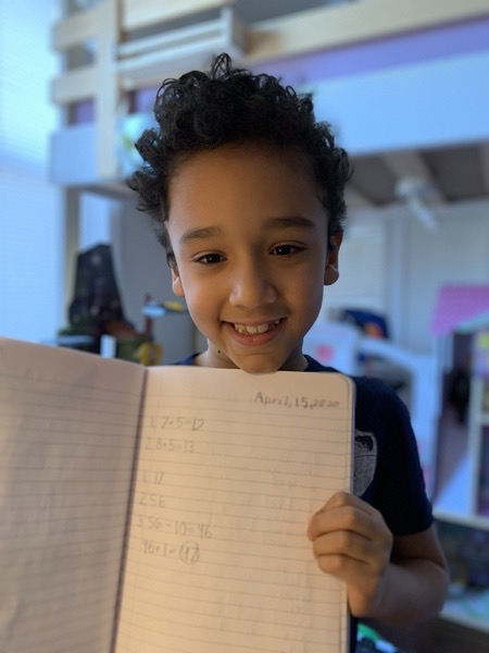 smiling boy shows his work