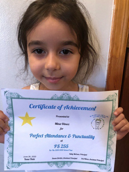 close up of smiling girl holding her attendance certificate