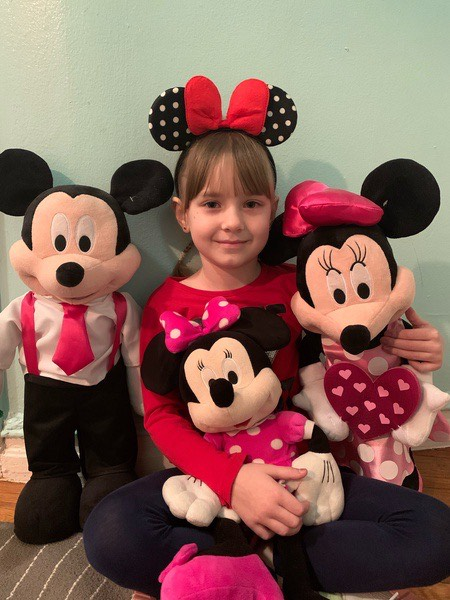 girl with ears and stuffed mickey and Minnie