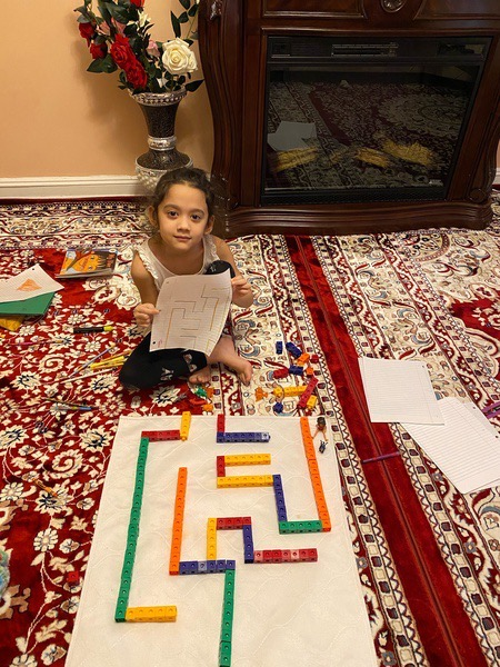 girl sits on the carpet near the maze she created