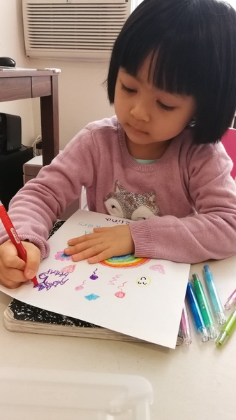 girls uses markers to draw a rainbow