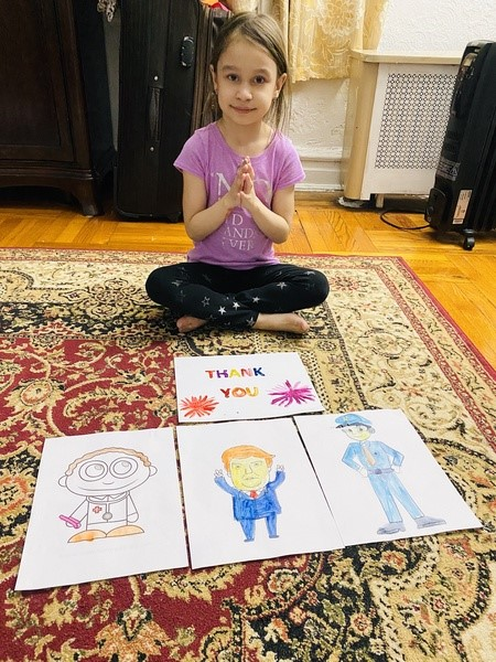 child sits on the floor with four pictures she drew
