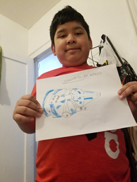 boy in red shirt shows his work