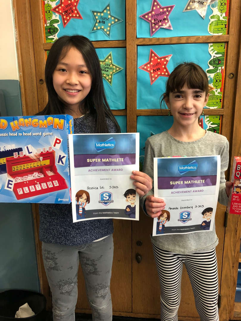Two girls hold games and certificates.