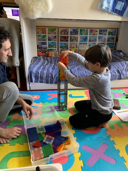 boy builds as his dad watches