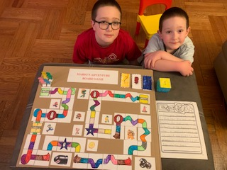 brothers sit near the board game they made