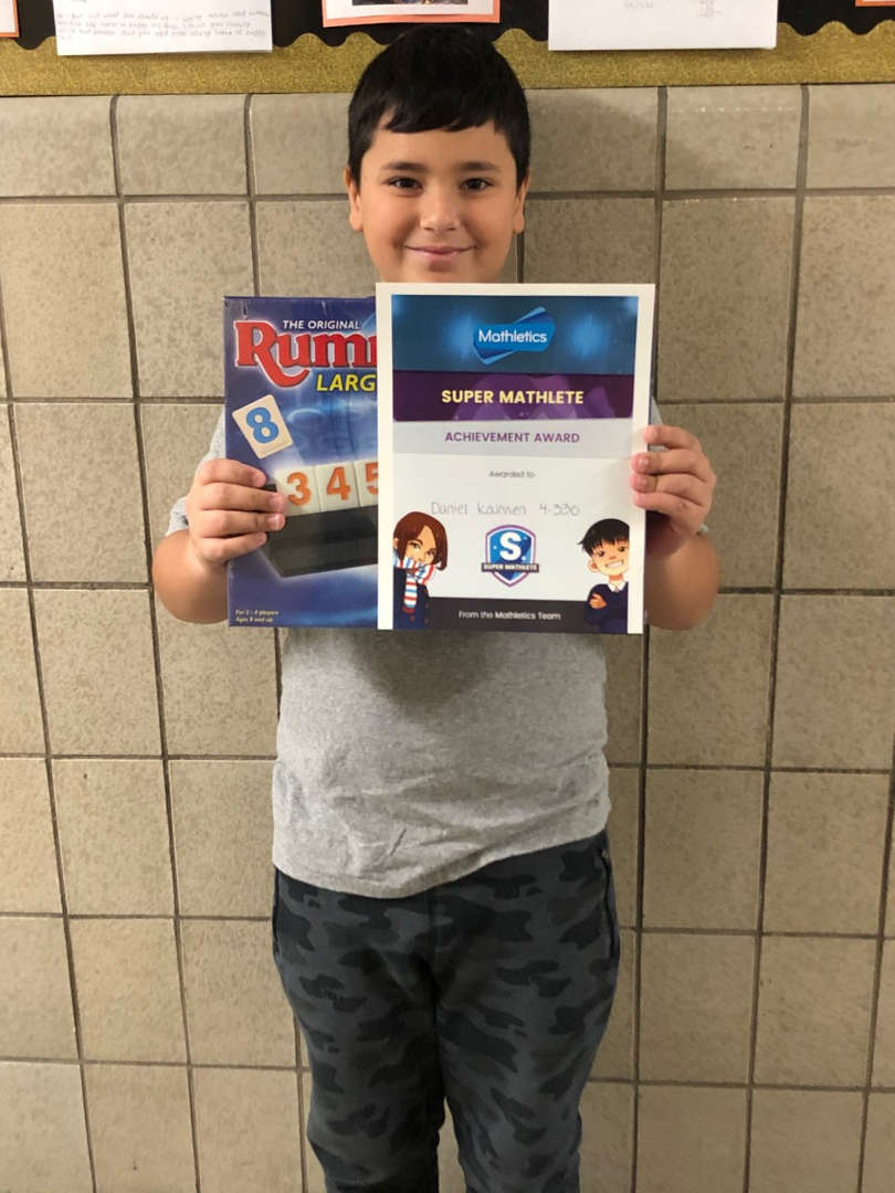 A student holds the game he won and a certificate for Mathletics.