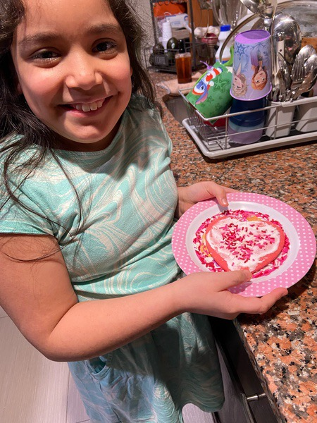 girl in green shirt with her decorated cookie