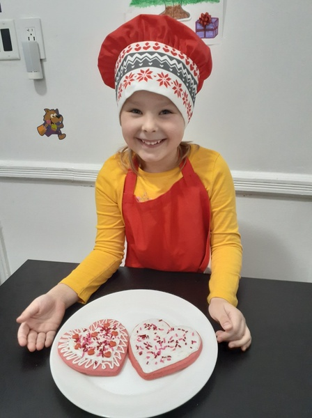 girl in apron showing her decorated cookies