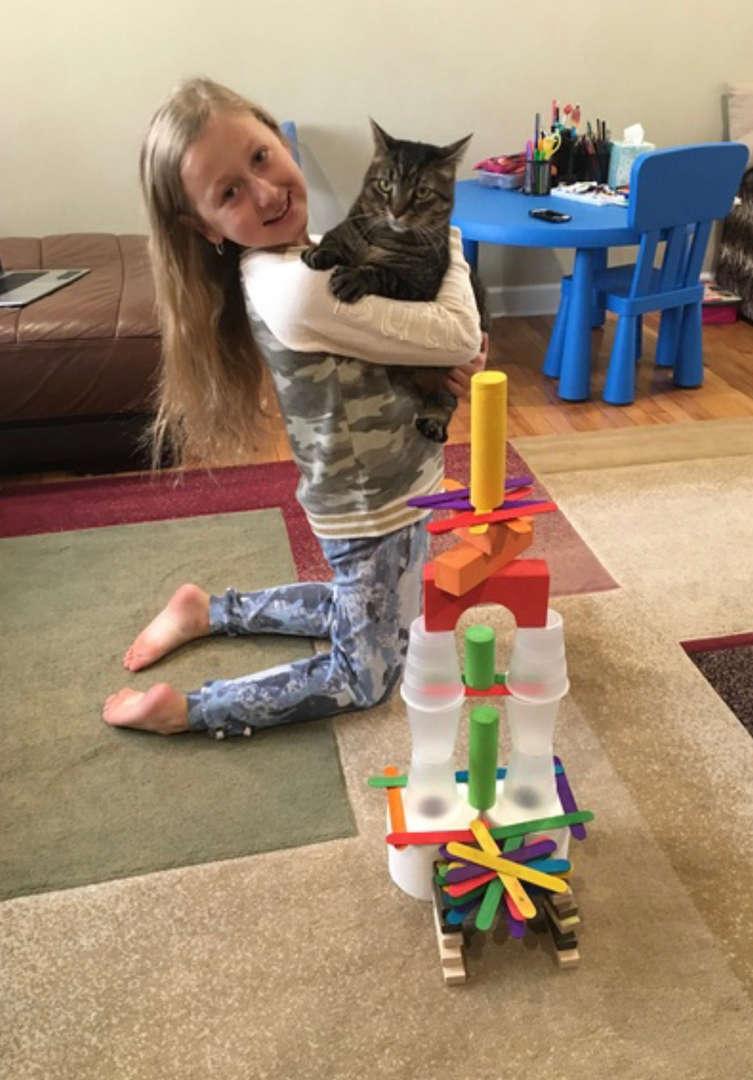 the child hugs a cat near their creation