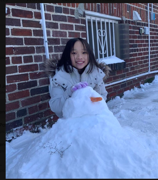a snowman with a carrot nose and a girl who built it