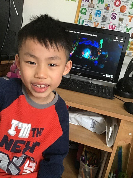 boy smiles in front of computer