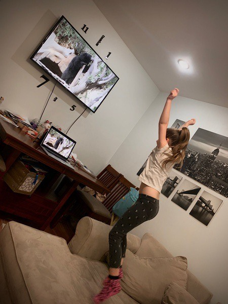 the girl jumps while watching the television
