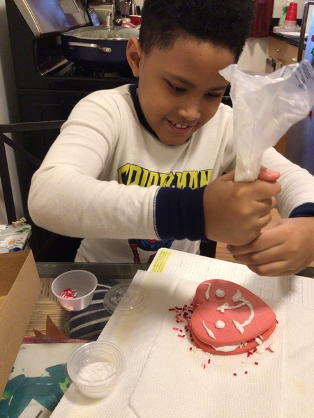 student putting white icing on her heart cookie