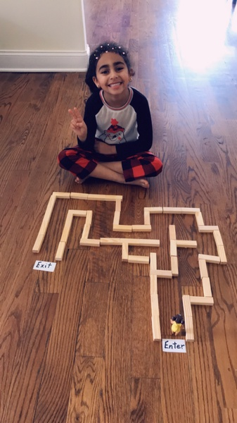 child sits with his legs crossed behind his maze