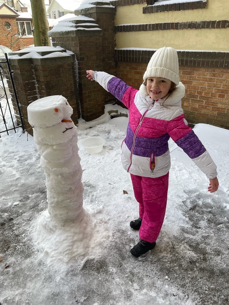 a girl next to a snowman almost as tall as her