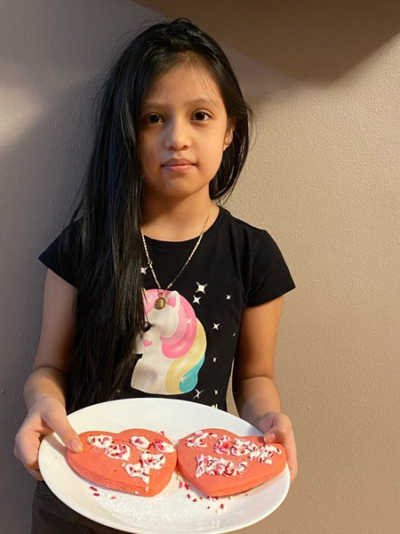 girl in unicorn shirt decorated cookies