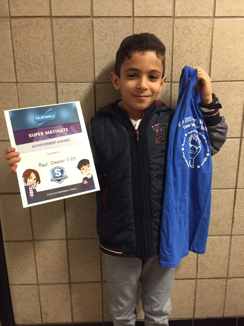 Student smiles as he holds his prizes.