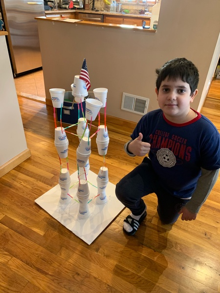 the boy gives a thumbs up next to his cup tower