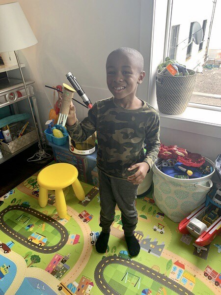 the child smiles showing his lego creation