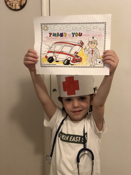 child wears a medical hat while holding a picture of an ambulance
