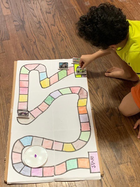child plays the board game he made on the floor