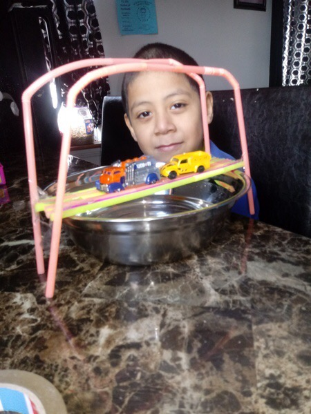the cars cross the bridge over a ball of water as the child looks at the camera