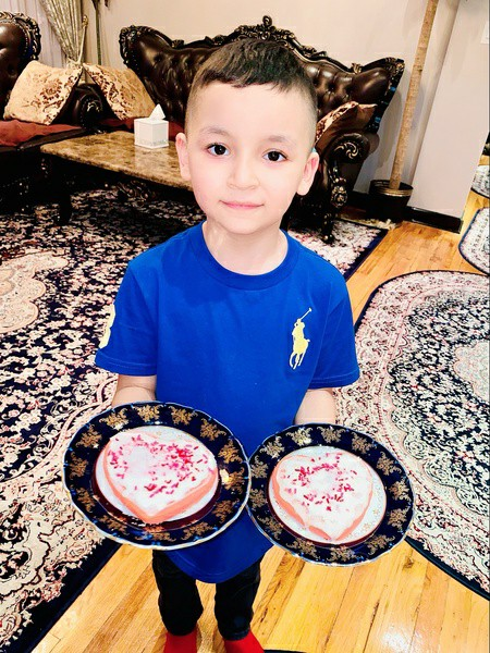 boy in blue shirt holds each decorated cookie in each hand