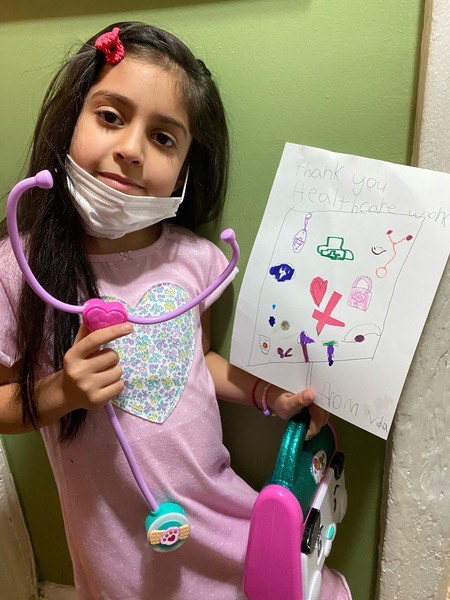 girl holds a toy and a thank you sign