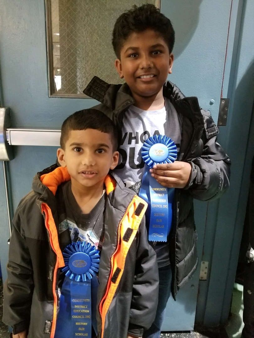 two boys pose with blue ribbon for winning in the history fair