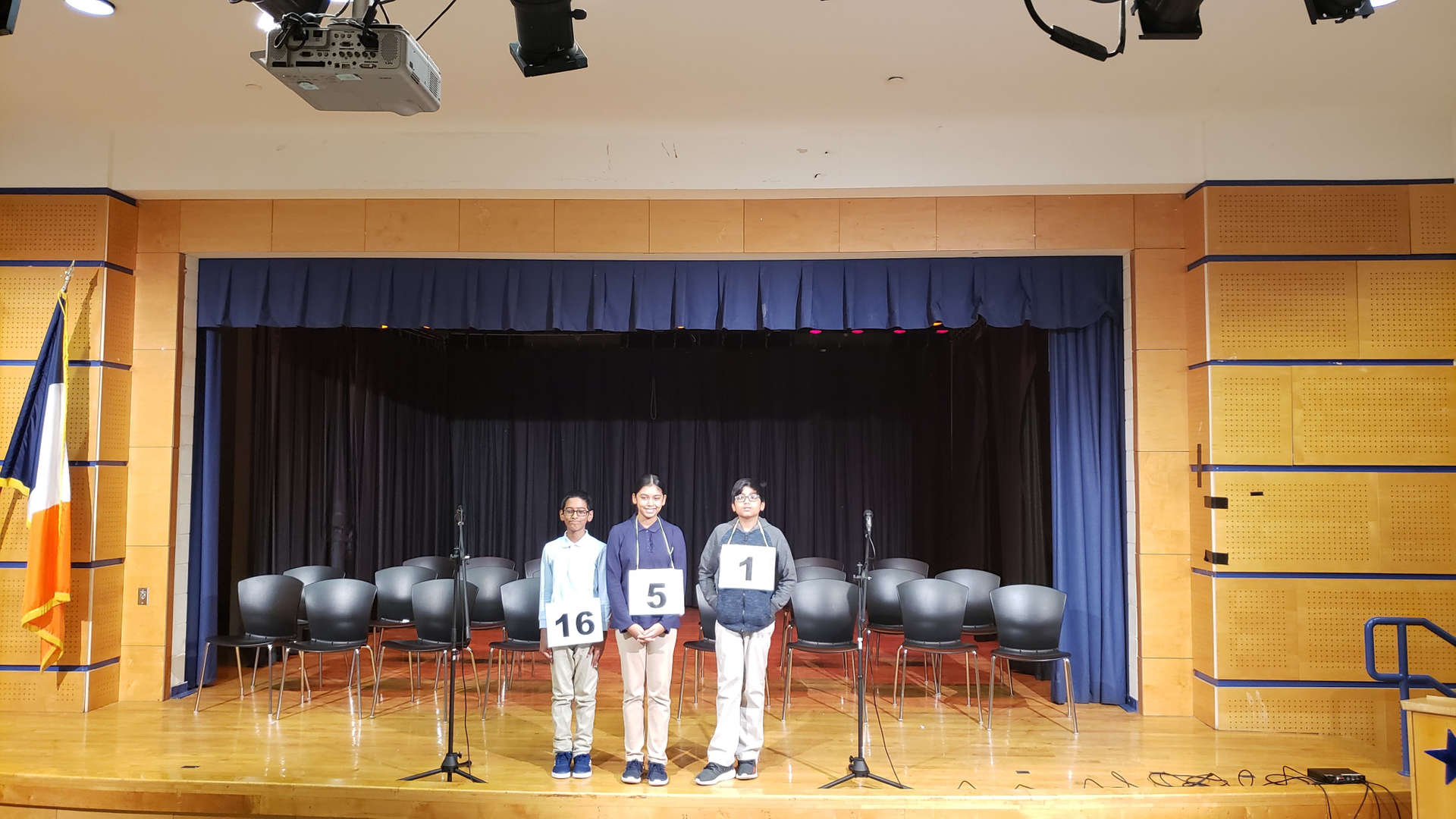three students finalist stand on stage after winning the school-wide spelling bee