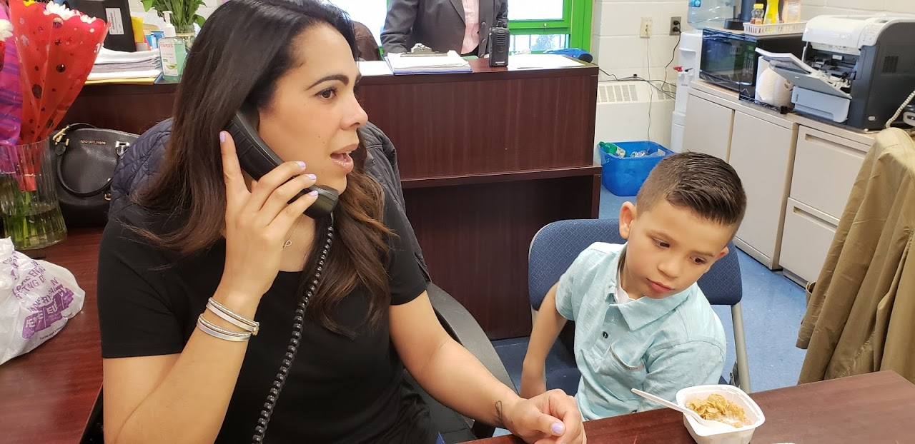 secretary answers phone as son watches what mom does at work