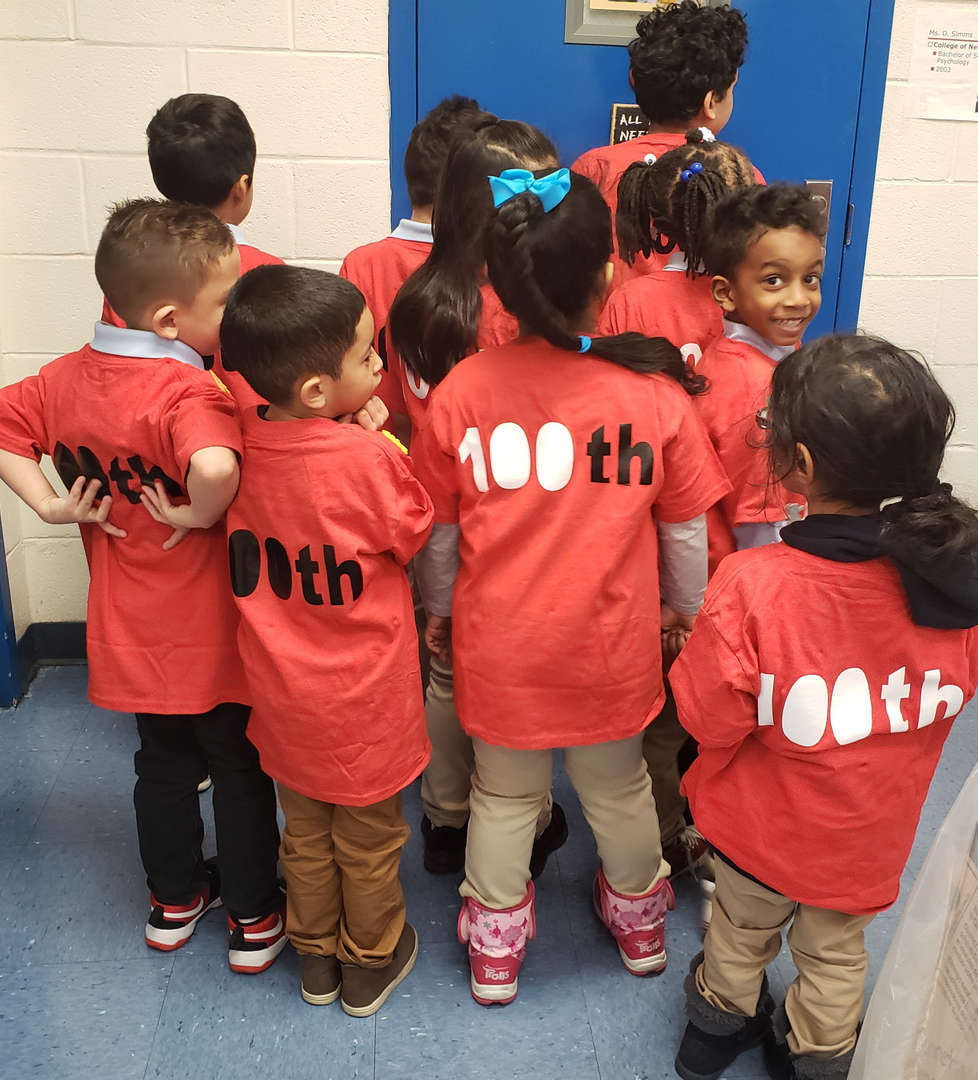 students pose for 100th day of school with orange t-shirts with 100 on back