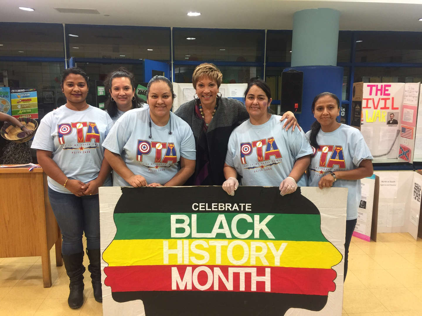 ladies pose with black history month banner