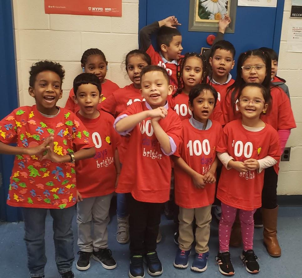 children with the number 100 on tshirts smile for the 100th day of school